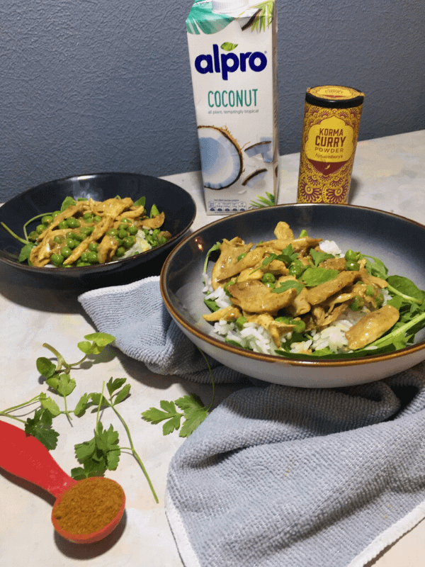 chicken korma in  two plates with spice blend