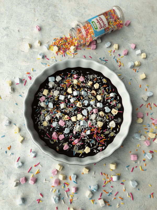 bowl of chocolate bark and spilled bottle of sprinkles